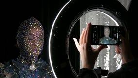 Hög-mode Modellen i bilden av en främmande flicka i en svart maskering, i att moussera bergkristaller, mousserar, metallfjärilar lager videofilmer