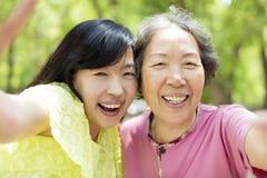 Hög moder och dotter som tar selfie fotografering för bildbyråer