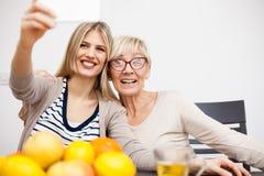 Hög moder och hennes dotter som ler och tar en selfie, medan sitta vid matställetabellen i ljust rum royaltyfri fotografi