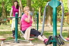 Hög och ung kvinna som övar lägre kropp på den utomhus- idrottshallen, sund livsstil arkivbild