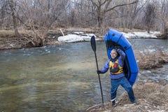Hög paddler som bär en packraft Royaltyfri Bild