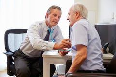 Hög patient som har medicinsk examen med doktor In Office royaltyfri fotografi