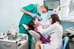 Hög pediatrisk tandläkare med sjuksköterskan som gör den tålmodiga flickan för tand- behandling som använder den tand- röntgenapp Arkivbilder