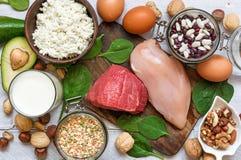Hög - proteinmat - höna, kött, spenat, muttrar, ägg, bönor och ost arkivfoto