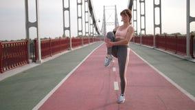Hög rödhårig mankvinnas sträckande muskler för ben arkivfilmer