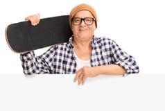 Hög skateboradåkare som rymmer en skateboard bak en panel Royaltyfria Foton
