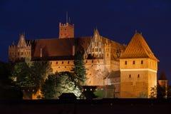 Hög slott av den Malbork slotten på natten Arkivfoto