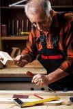 Hög snickare som arbetar i hans seminarium Royaltyfri Foto