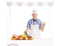 Hög sodavattenfjant som rymmer ett exponeringsglas av lemonad Royaltyfri Fotografi