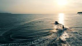 hög solnedgång för jpgupplösningshav Två motorbåtar surfar till och med havsfjärden lager videofilmer