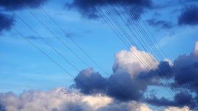 H?g-sp?nning elektriska tr?dar mot en bl? himmel med att sv?va att flyga iv?g f?r moln och f?r f?glar lager videofilmer