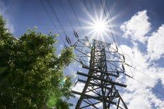 Hög spänning fodrar, och den ljusa solen illustrerar sommarmaktbehov Arkivbilder