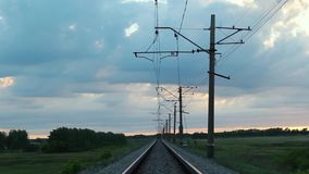 Hög-spänning knyter kontakt över järnvägsspåret i fältet stock video