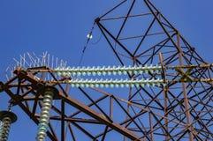 Hög-spänning kraftledning mot den blåa himlen med moln royaltyfri foto