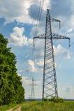 Hög-spänning kraftledning mot den blåa himlen med moln arkivbild