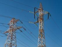 Hög-spänning kraftledningar arkivbild