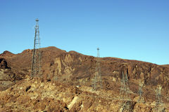 Hög-spänning kraftledningar från dammsugarefördämningen Royaltyfri Foto