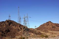 Hög-spänning kraftledningar från dammsugarefördämningen Royaltyfri Fotografi