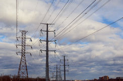 Hög-spänning kraftledningar mot stormig himmel Royaltyfria Foton