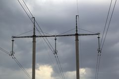 Hög-spänning kraftledningar och en transformator med trådar mot den gråa molniga himlen royaltyfri bild