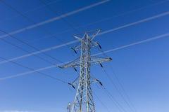 Hög-spänning kraftledningar och pylon mot blå himmel II Arkivfoto