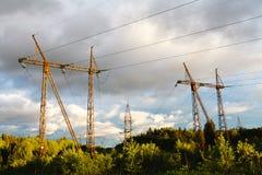 Hög-spänning kraftledningar på solnedgången elektricitetsfördelningssta royaltyfri fotografi