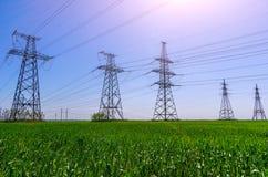 Hög-spänning kraftledningar på solnedgången Elektricitetsfördelningsstation royaltyfri foto
