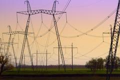 Hög-spänning kraftledningar på solnedgången Elektricitetsfördelningsstation Elektriskt överföringstorn för hög spänning arkivbild