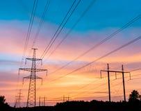 Hög-spänning kraftledningar på solnedgången Elektricitetsfördelningsstation Elektriskt överföringstorn för hög spänning royaltyfria bilder