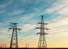 Hög-spänning kraftledningar på solnedgången Elektricitetsfördelningsstation Elektriskt överföringstorn för hög spänning royaltyfri foto