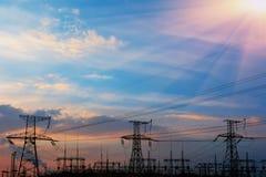 Hög-spänning kraftledningar på solnedgången Elektricitetsfördelningsstation Elektriskt överföringstorn för hög spänning royaltyfria foton