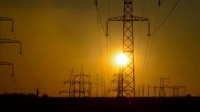 Hög-spänning kraftledningar på soluppgång lager videofilmer