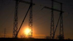 Hög-spänning kraftledningar på soluppgång stock video