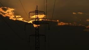 Hög-spänning kraftledningar på soluppgång arkivfilmer