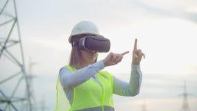 Hög-spänning kraftledningar som kontrolleras av en kvinnlig tekniker som använder virtuell verklighet för att kontrollera makt al stock video