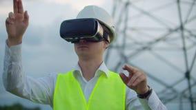 Hög-spänning kraftledningar som kontrolleras av en manlig tekniker som använder virtuell verklighet för att kontrollera makt alte arkivfilmer