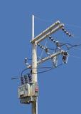 Hög spänning Pole med transformatorn som isoleras på blå bakgrund Royaltyfri Foto