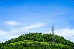 Hög-spänning poler med trådar på kullen Kraftledning på pylonen Arkivbild
