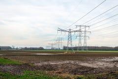 Hög-spänning pyloner och hög-spänning linjer för transportering av elektricitet från kraftverket i bakgrunden royaltyfri bild