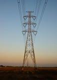 Hög-spänning torn på skymning Arkivfoto
