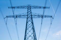 Hög spänningselektricitetspylon i blå himmel Arkivbild