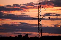 Hög spänningselektricitetspylon på solnedgången Arkivfoto