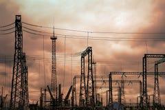 Hög spänningselkraftstation - elektriska poler och linjer på bakgrund för molnig himmel för aftonguling royaltyfria foton