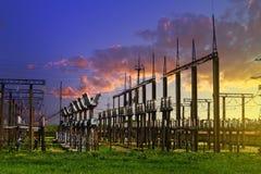 Hög spänningselkraftstation - elektriska poler och linjer på blå bakgrund för molnig himmel för solnedgång royaltyfri fotografi