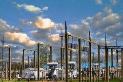 Hög spänningselkraftstation - elektriska poler och linjer på blå molnig himmel med vaniljmolnbakgrund Royaltyfria Bilder