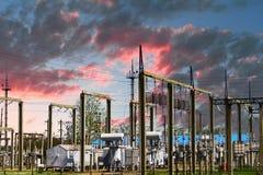 Hög spänningselkraftstation - elektriska poler och linjer på härlig rosa bakgrund för molnig himmel royaltyfri bild