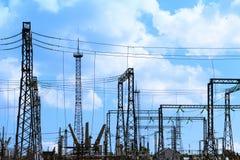 Hög spänningselkraftstation - elektriska poler och linjer på ljus blå bakgrund för molnig himmel royaltyfri bild