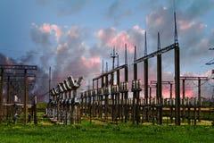 Hög spänningselkraftstation - elektriska poler och linjer på trevlig röd bakgrund för molnig himmel för solnedgång fotografering för bildbyråer