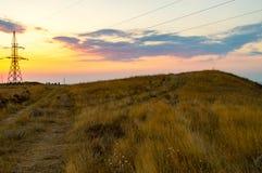 Hög spänningslinje som omges av vetefält på solnedgången Royaltyfria Bilder