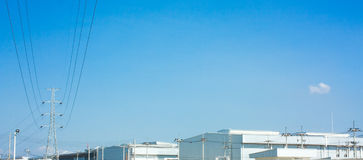Hög spänningspol till fabrikshimmelutrymme arkivfoto